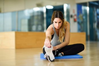 Young woman working out indoors. Female stretching their legs on the floor of a gym.