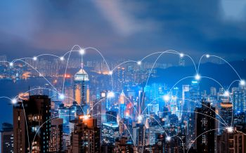 Digital network connection lines of Hong Kong Downtown and Victoria Harbour. Financial district in smart city in technology concept. Skyscraper and high-rise buildings. Aerial view at night.