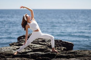 Young woman doing yoga in the beach. Female wearing white sport clothes in warrior at sun figure with defocused sea background.