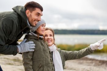 family, leisure and people concept - happy mother, father and little daughter on autumn beach. happy family on autumn beach