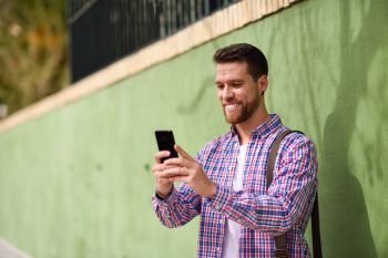 Young man looking at his smart phone in urban background. Lifest. Young man looking at his smart phone and smiling in urban background. Guy wearing casual clothes. Lifestyle concept.