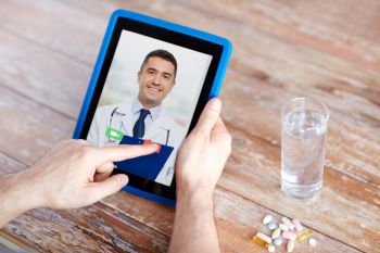 medicine, technology and healthcare concept - close up of patient with pills and water on table having video chat with doctor on tablet pc computer. patient having video chat with doctor on tablet pc