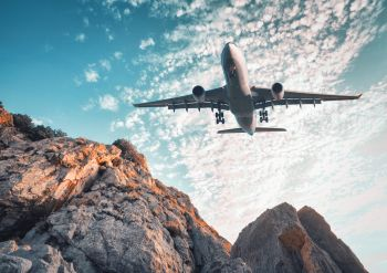 Big airplane is flying over rocks at sunset in summer. Landscape with  landing passenger airplane, mountains, colorful blue sky with clouds. Business travel. Commercial plane. Vintage toning. Aircraft