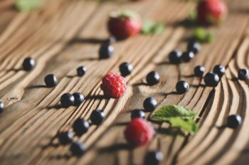 Ripe organic Raspberries and Blueberries on the top of wooden table