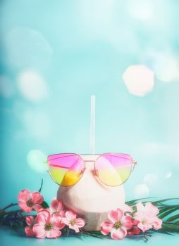 Fresh coconut cocktail with pink sunglasses with tropical leaves and flowers at blue background with bokeh. Tropical vacation. Summer holiday. Beach party