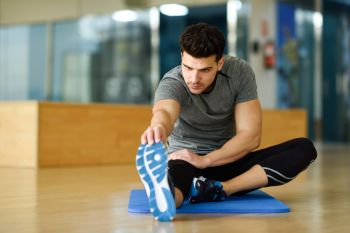 Young man working out indoors. Male stretching their legs on the floor of a gym.