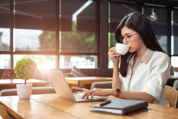 Asian working woman using laptop and drinking coffee in cafe. People and lifestyles concept. Technology and business theme. Freelance and occupation theme. Workaholic in overnight concept.