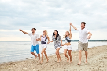 summer, holidays, sea, tourism and people concept - group of smiling friends in sunglasses running on beach