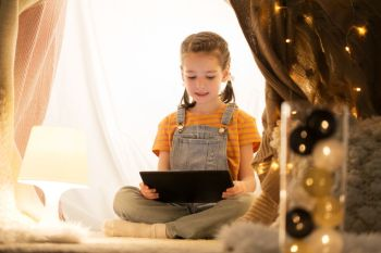 childhood, technology and hygge concept - happy little girl with tablet pc computer in kids tent at home. little girl with tablet pc in kids tent at home