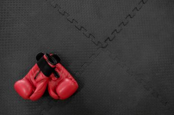 boxing gloves hang on nail on texture wall with copy space for text. Retirement concept