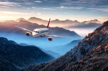 Airplane is flying over mountains in fog at colorful sunset in summer. Landscape with passenger airplane, hills in low clouds, blue sky. White aircraft. Business travel. Commercial plane. Aerial view