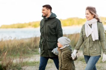 family, leisure and people concept - happy mother, father and little daughter walking along autumn beach. happy family walking along autumn beach