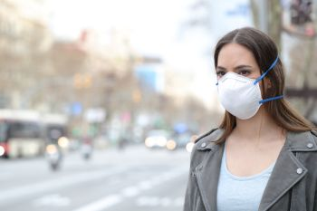 Serious woman wearing protective mask avoiding pollution looking at city road