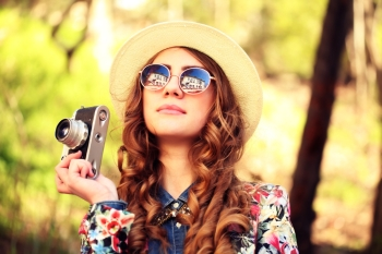 Outdoor summer lifestyle portrait of pretty young woman having fun in the city. Photographer making pictures in hipster style glasses and hat. Photo toned style Instagram filters.