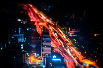 Tilt shift blur effect. Futuristic night cityscape aerial view panorama with illuminated skyscrapers and city traffic across streets. Bangkok, Thailand