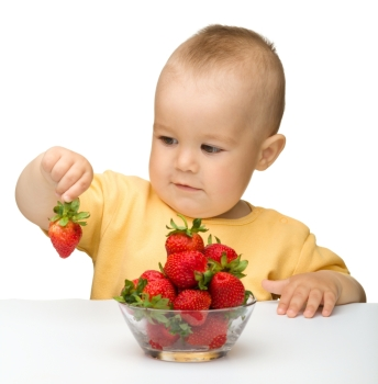 Happy little girl with strawberries, isolated over white