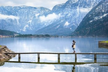 Travel destination theme image with a woman walking on a narrow deck that crosses the Hallstatter lake, surrounded by the Austrian Alps mountains.