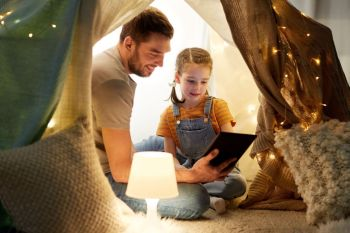 family, hygge and technology concept - happy father and little daughter with tablet pc computer in kids tent at night at home. family with tablet pc in kids tent at home