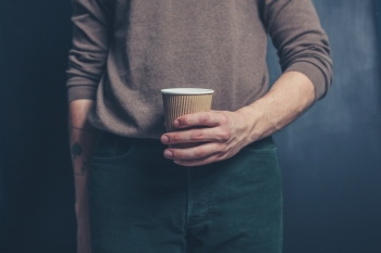 Young man is  holding a brown paper cup