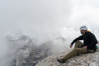 young male mountain climber on a Dolomite mountain peak enjoying the view
