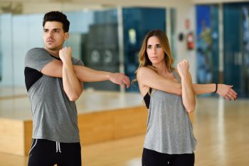 Young woman and man working out indoors. Two people stretching their arms in a gym.