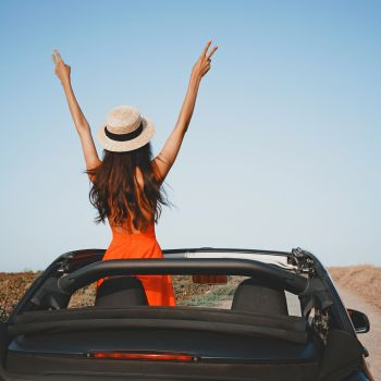 Outdoor lifestyle photo of beautiful happy woman in car cabriolet. Holiday and travel. Summer trip. Freedom, youth and carefree