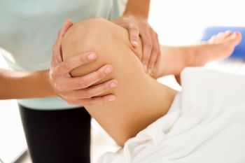 Medical massage at the leg in a physiotherapy center. Female physiotherapist inspecting her patient. Close-up photograph.