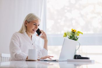 Woman talking on the phone, using laptop. Working from home, freelancing, online job.. Woman talking on the phone, using laptop.