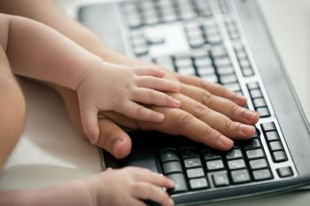 Closeup of fathers and baby's hands on computer keyboard