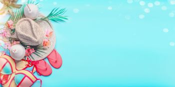 Top view of woman's summer beach accessories: bikini,  flip flops, sunglasses, straw hat, creole earrings, with palm leaves and tropical flowers on turquoise blue background, banner with copy space