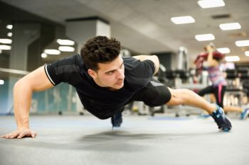 Attractive man doing pushups in the gym. Guy wearing sportwears clothes.
